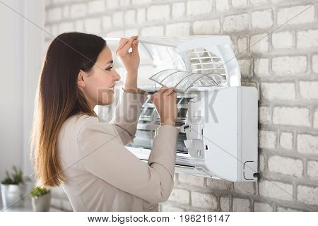 Young Smiling Woman Cleaning The Air Conditioner Attached On Wall