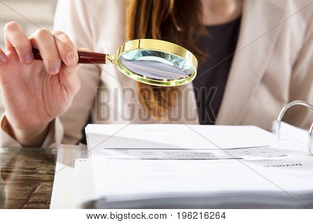 Close-up Of A Businesswoman Examining Invoices With Magnifying Glass