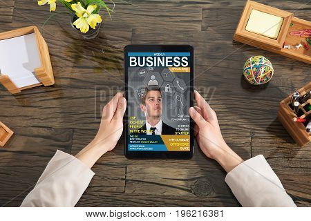 A Businessperson Looking At Business Magazine On Digital Tablet At Office Desk