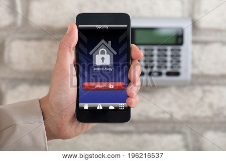 A Person's Hand Holding Smartphone For Disarming Security System Of Door