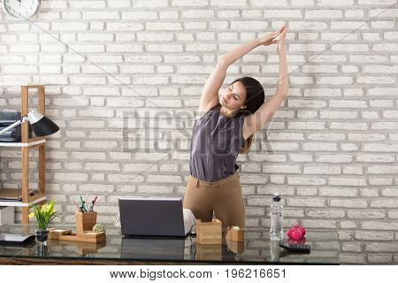 Young Businesswoman Stretching At Workplace In Office
