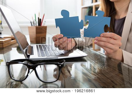 Businesswoman Showing Blue Jigsaw Puzzle With Laptop And Eyeglasses On Desk In Office