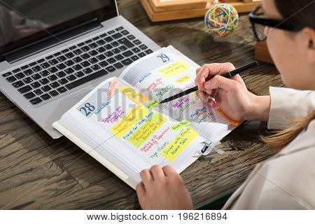 Close-up Of A Businessperson Writing Schedule In Diary On Wooden Desk