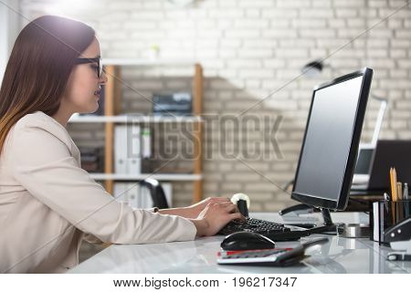 Smiling Young Businesswoman Typing On Keyboard Using Computer At Workplace In Office