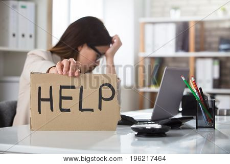 A Depressed Businesswoman Holding Help Sign On Desk At Workplace In Office