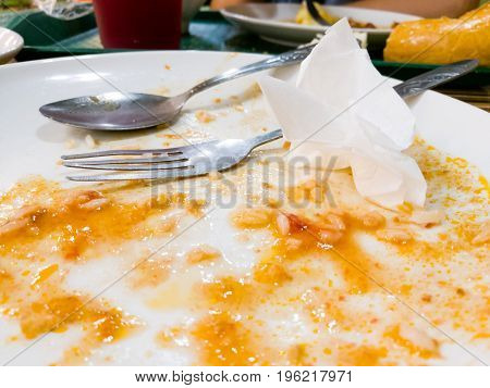 Dirty white plate with eaten food in a cafe .