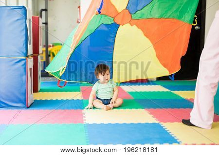 Baby Looking At A Colorful Parachute