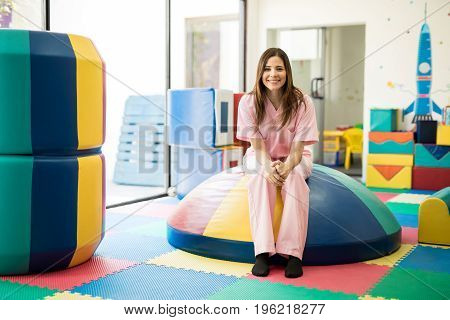 Portrait of a beautiful young woman working as a therapist in a children physical therapy and early stimulation school