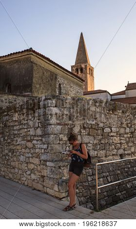 POREC CROATIA - JULY 14: Female tourist consulting the city guide in Porec on July 14 2017