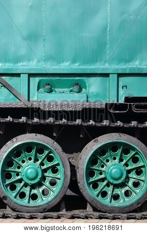 Side View Of The Vehicle On A Caterpillar Track With Black Tracks And Green Wheels And A Side Metal