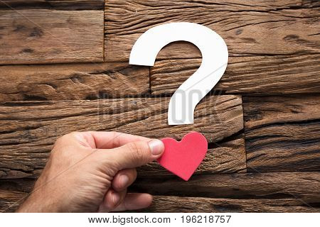 Closeup of hand holding question mark with heart on wood