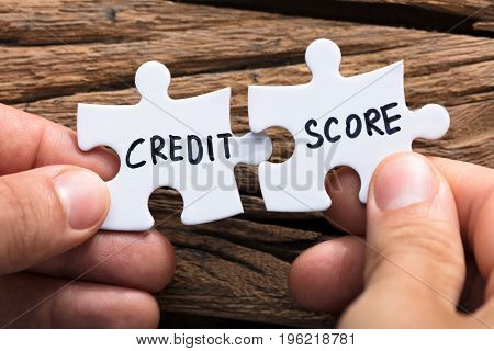 Closeup of hands connecting credit score jigsaw pieces against wood
