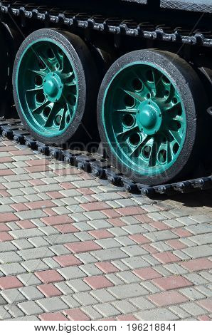 A Military Vehicle On Caterpillar Tracks Stands On A Square Of Paving Stones. Photo Of Green Caterpi