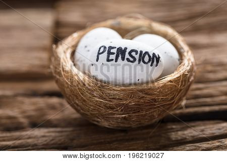 Closeup of pension written on white egg in nest on wood