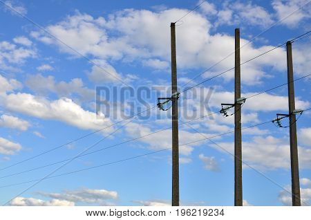 Concrete Pole With Wires Of Power Line Against The Background Of Blue Cloudy Sky