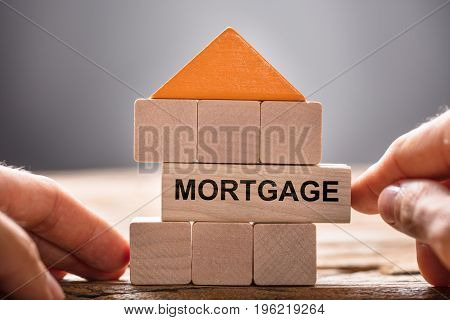 Closeup of hands building house model with mortgage block on wood