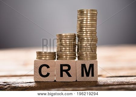 Closeup of CRM text written on wooden blocks with stacked coins