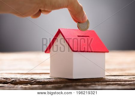 Closeup of hand putting coin in house piggy bank on wood
