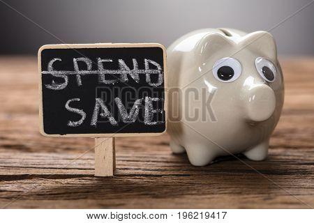 Closeup of piggybank by spend save sign on wood representing saving plan