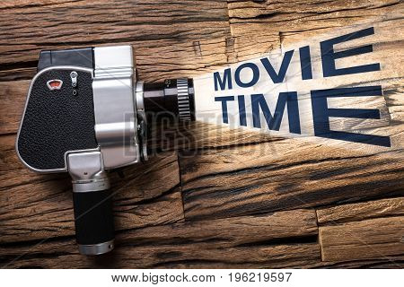 Closeup of movie camera emitting light with text movie time on wood
