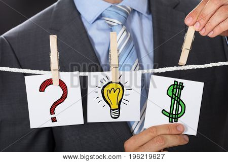 Midsection of businessman pinning dollar sign card by lightbulb and question mark signs on clothesline