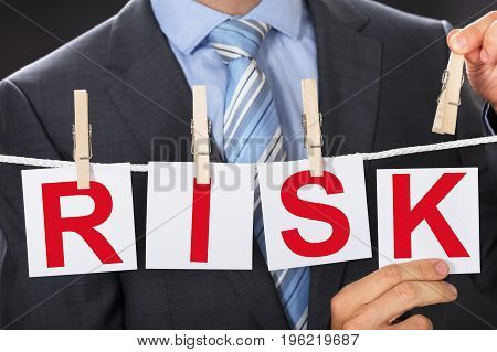Closeup midsection of businessman pinning RISK cards on clothesline