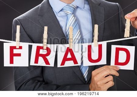 Closeup midsection of businessman pinning FRAUD cards on clothesline