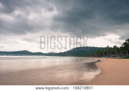 EL NIDO PALAWAN PHILIPPINES - JANUARY 20 2017: Lonely man walking at Nacpan Beach during cloudy day. Houses and coconut trees composes the scene.