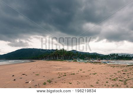 Wide angle view of Nacpan Beach in a cloudy day. Nobody boats and coconut trees in this tropical island.