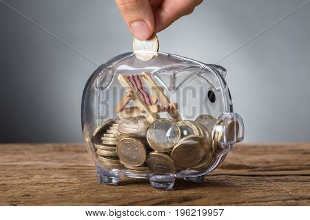 Closeup of hand putting coin in transparent piggy bank with deck chair