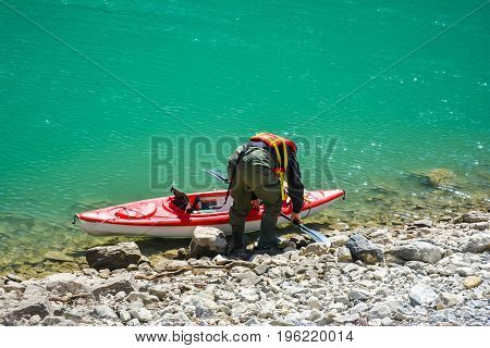 A Kayaker Getting Ready to Set Sail on a Green Lake