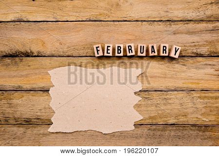 February - Calendar Month In Wooden Block Letters With Handmade Paper For Copy Space On Wooden Backg