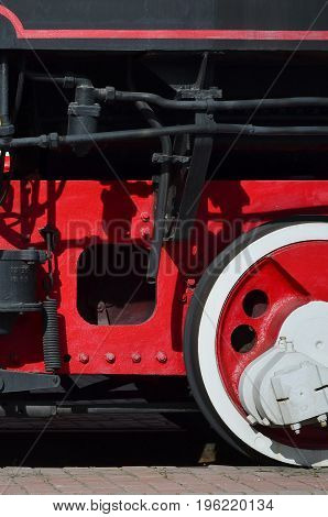 Wheels Of The Old Black Steam Locomotive Of Soviet Times. The Side Of The Locomotive With Elements O