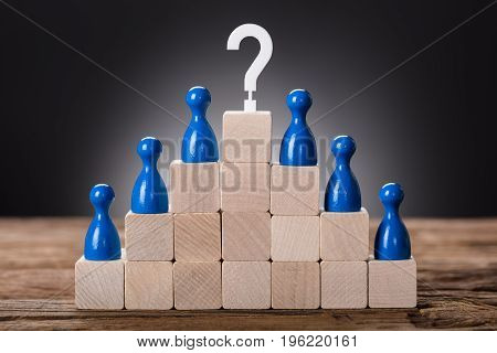 Closeup of blue pawn figurines on wooden blocks with question mark sign on top