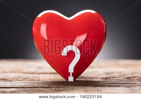 Closeup of question mark and heart on wooden table