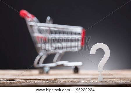 Closeup of question mark with shopping cart in background on table