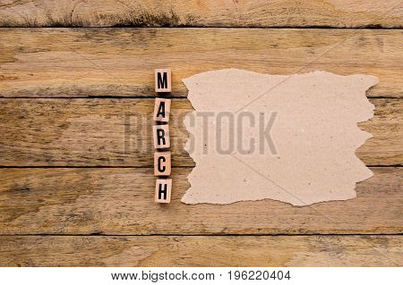 March - Calendar Month In Wooden Block Letters With Handmade Paper For Copy Space On Wooden Backgrou