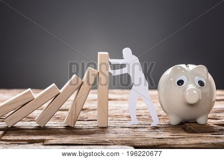 Closeup of paper man stopping wooden domino blocks by piggy bank on table