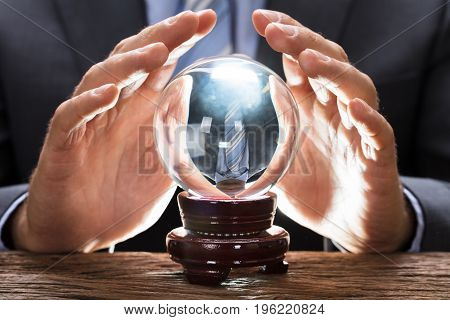 Midsection of businessman covering crystal ball at wooden table