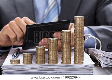 Midsection of businessman calculating invoice with stacked coins in increasing order at table