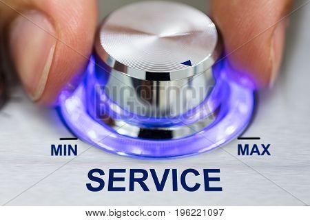 Cropped image of hand turning illuminated metallic knob by service text