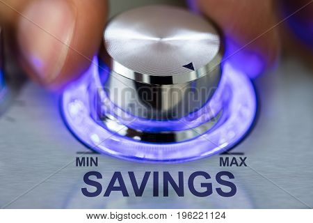 Cropped image of hand turning illuminated metallic knob by savings text