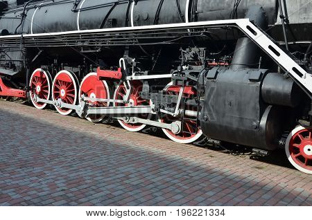 Wheels of the old black steam locomotive of Soviet times. The side of the locomotive with elements of the rotating technology of old trains