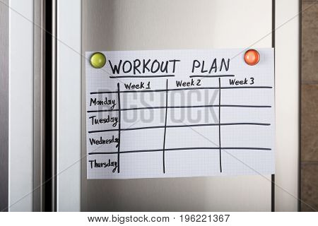 Closeup of weekly and daily workout plan paper attached with magnetic thumbtacks on metal