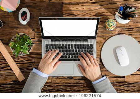 Elevated View Of A Businessperson Using Laptop With Blank White Screen In Office