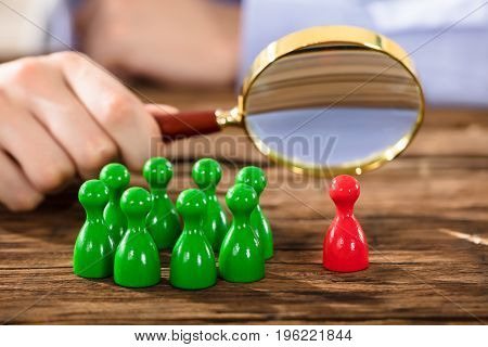 Close-up Of A Human Hand Examining Red Plastic Figure With Magnifying Glass Over Wooden Desk