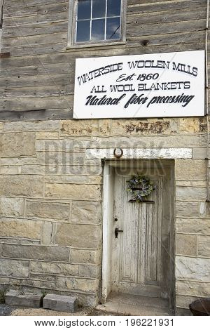 Woodbury PA USA - July 15 2017 : Sign on stone wall over wooden doorway of Waterside Woolen Mills.