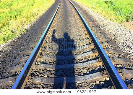 The railway, the walking shadow of a man, the movement in front of