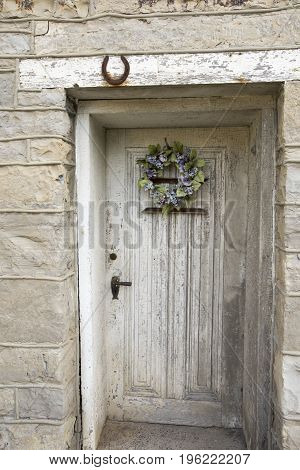 Floral wreath on wooden door in stone wall of rustic old building.