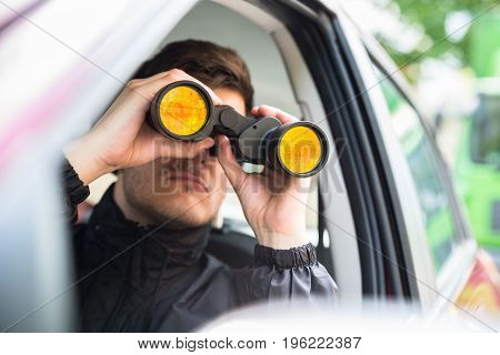 Close-up Of A Man Sitting Inside Car Looking Through Binocular